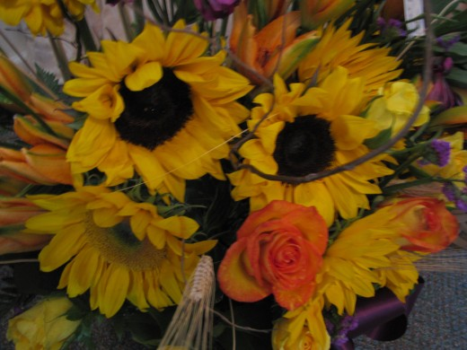 This flower arrangement has sunflowers with roses, daylilies, wheat heads, and a touch of purple flowers for accent.