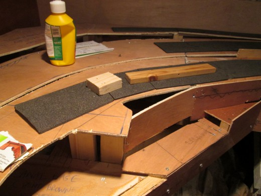 A couple of lengths of wood hold down the unsecured lengths of foam to show the transition curves on the two lower levels. Below left is where a canal tunnel portal will be added