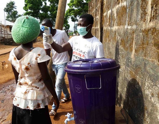 A healthcare worker takes a patient's temperature to determine if she might have Ebola.