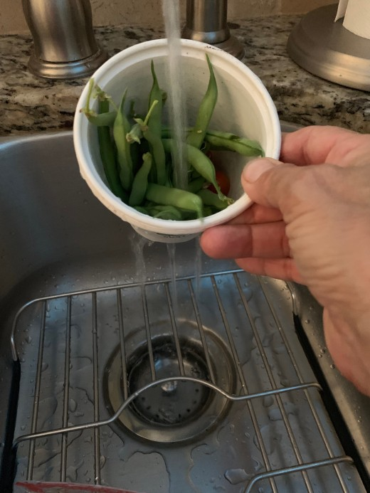 Rinsing green beans and cherry tomatoes in a small container.  Note the drainage.