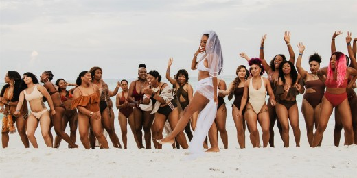 Bride with her 34 bridesmaids on the beach