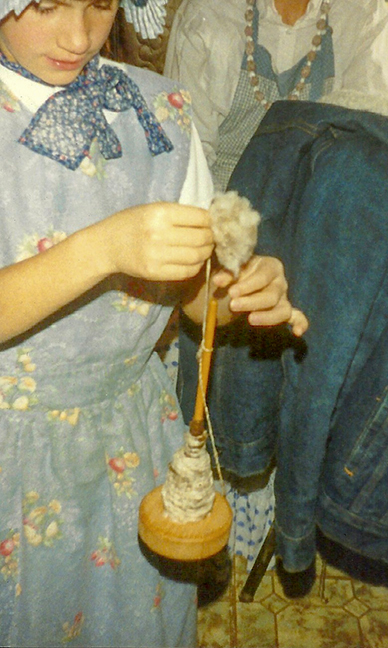 Spinning wool with a drop spindle.