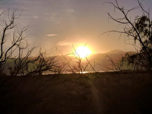 Looking across Salton Sea at sun setting behind Santa Rosa Mountains
