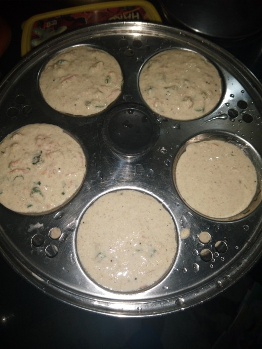 Pour the batter in the greased idli moulds.