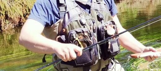 Man wearing a fly fishing vest.