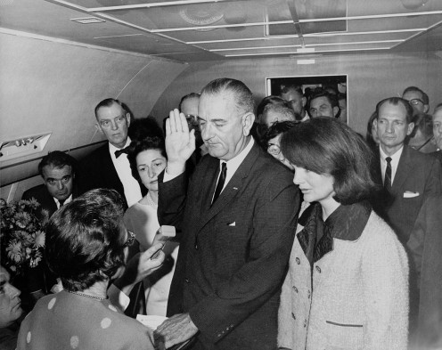 Vice President Lyndon Johnson being sworn in as President after John F. Kennedy was assassinated, Mrs. Kennedy to the right.