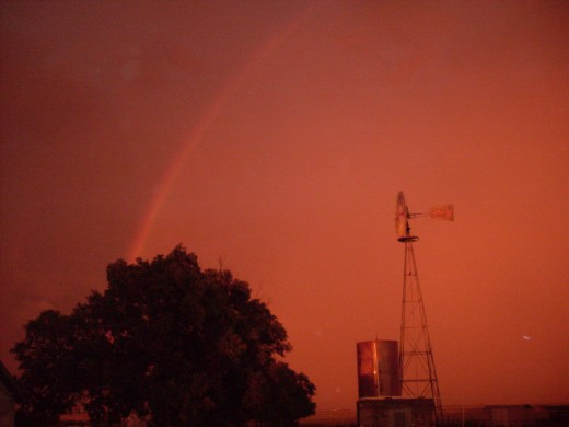 I've been trying for years to capture a rainbow. I finally did it!  That's a working windmill in the foreground, with its holding tank for water.