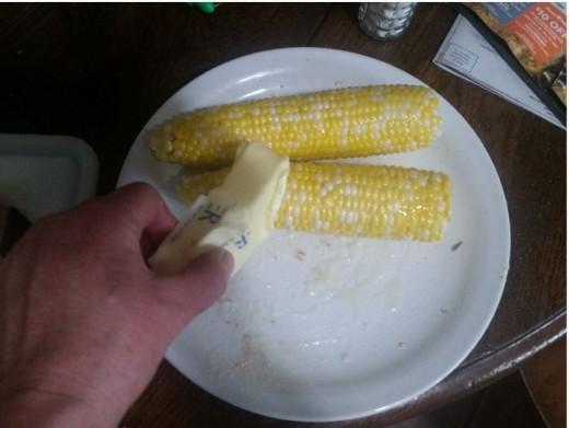 smear melting butter across corn
