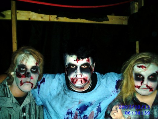 Three individuals wearing clothing from their closets and painted faces of Zombies.of horror.