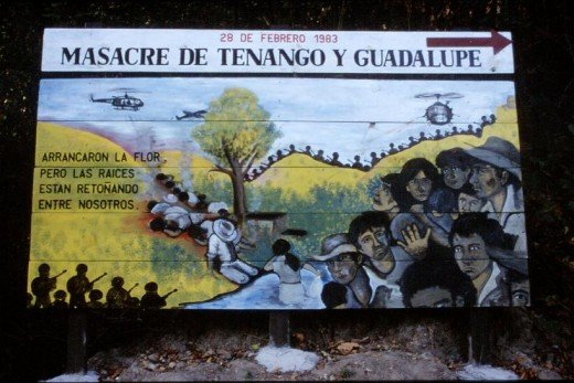 """A billboard serving as a reminder of one of many massacres that occurred during the Civil War in El Salvador. The Spanish inscription to the left reads in English: 'They tore out the flower, however the roots are sprouting among us.' - Wikipedia"