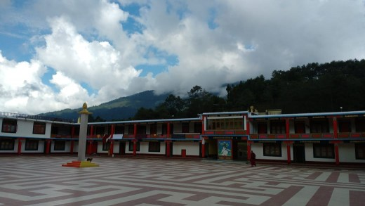 A magnificent monastery with lush green hills at the backdrop and wandering clouds. Calmness dominates the place.