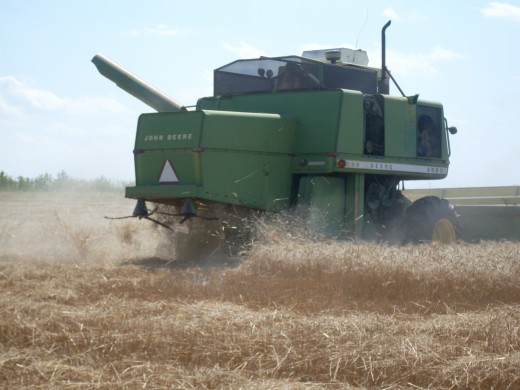 Two spreaders with flails scatter the straw out behind the combine.