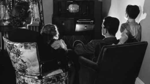 A family gathers around the living room TV, the chief threat to Hollywood over the last seventy years