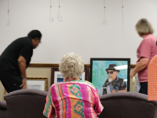 Judges scrutinizing work at an art show before the hanging.