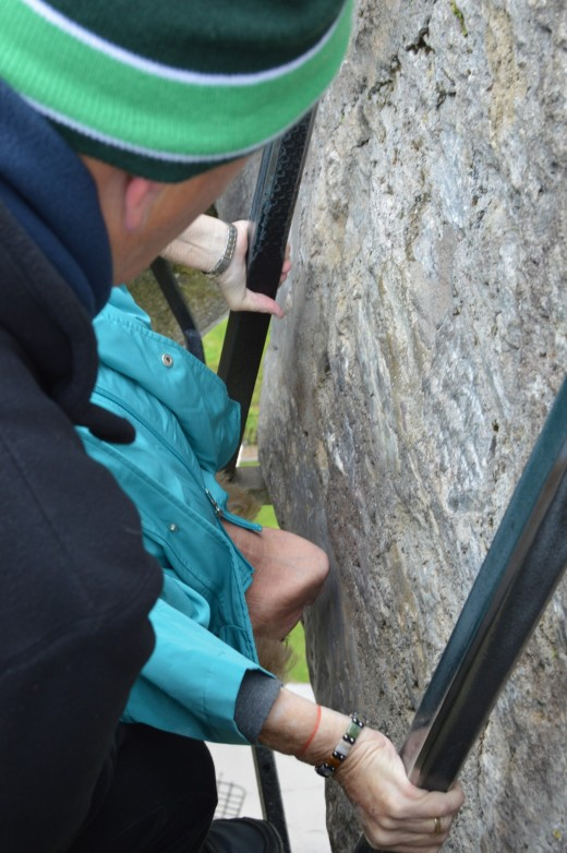 Some people actually kiss the stone; others (like this photographer) wonder who else has kissed it and pretend to kiss it instead. Kissers grab bars to prevent a fall through the hole to the ground below. A castle employee holds on to the kisser.