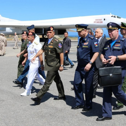 "Venezuelan Defense Minister Vladimir Padrino (4th from left) walks with Venezuelan and Russian military personnel, as Tu-160 is seen in the background at the Maiquetía ""Simón Bolívar"" International Airport in Caracas, Venezuela, on December 10. Venez"