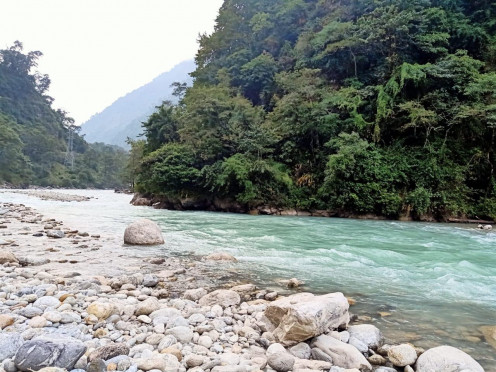 The river flowing through stones with lush green hills in the backdrop