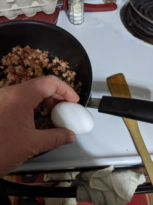 Tap egg on side of pan to break.