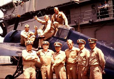 Some cast members of Midway, 1976, pose on the USS Lexington in front of an F4F Wildcat.