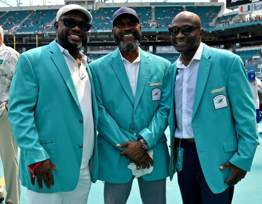 Former Miami Dolphins running back, Tony Nathan (center), stands with former wide receivers, Mark Duper (left) and O.J. McDuffie (right), prior to a 2018 game against the Oakland Raiders at Hard Rock Stadium.