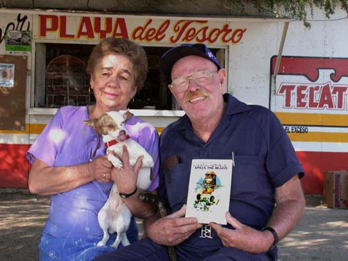 "A brilliant yet simple man:  Jimmy with Lupe and ""Mini"" In front of store and holding copy of book."