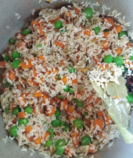 Mix rice with vegetables and spices.