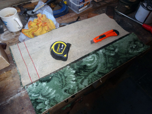 Cutting the carpet to size to fit into the pockets of the modified remote control holder.