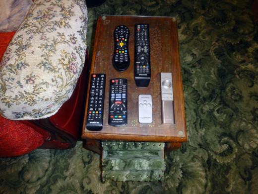 The modified remote control holder attached to the leading edge of the side table, with the remotes on the table and ready to place into the pockets.