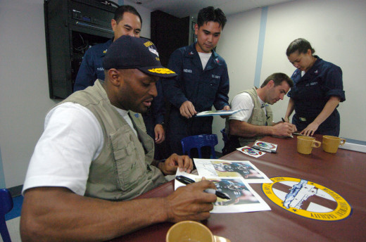 Amani Toomer and Kurt Warner sign autographs for sailors aboard the hospital ship USNS Mercy, 2005.