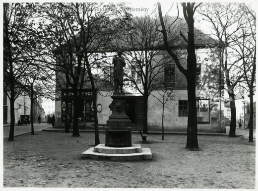 The Hébe well at Hess András Square, and next to it 3 Hess András Square, the Red Hedgehog house.