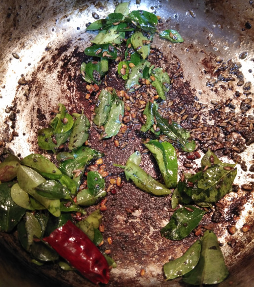 In the same pan again heat 1-2 teaspoons of oil.  Then add mustard seeds, cumin seeds, let them splutter. Then add methi or fenugreek seeds, dry red chilies, curry leaves and hing. Fry.
