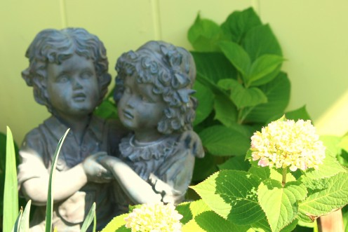 Further into the garden, statues and figurines are nestled into the foliage and flowers.