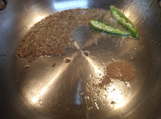 In a pan or pot add oil or ghee or butter. Add cumin seeds, hing and green chilies. Allow cumin seeds to crackle.