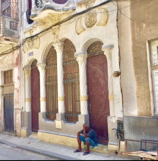 A man resting on the doorstep of a Baroque building which still has conserved its beauty.