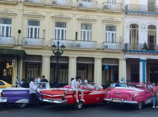 Young men offering tourists a road trip with a beautiful, shining classic American car. Find your car and ask for a trip along the Malecón to enjoy the sunset.