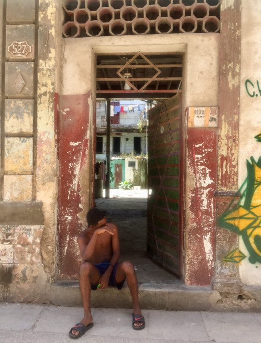 Young boy sitting on the doorstep in front of his home. What will the future bring?
