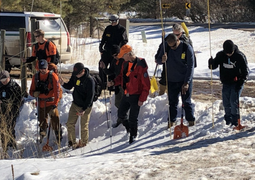 Searchers from the El Paso County Sheriff's Office search for Gannon Stauch's body with probes and shovels.