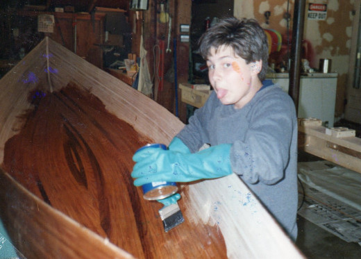 Scott applying resin to interior of canoe and sticking out his tongue at the camera man.