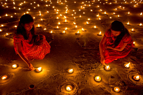 Diyas (earthen lamps) being lit on Diwali