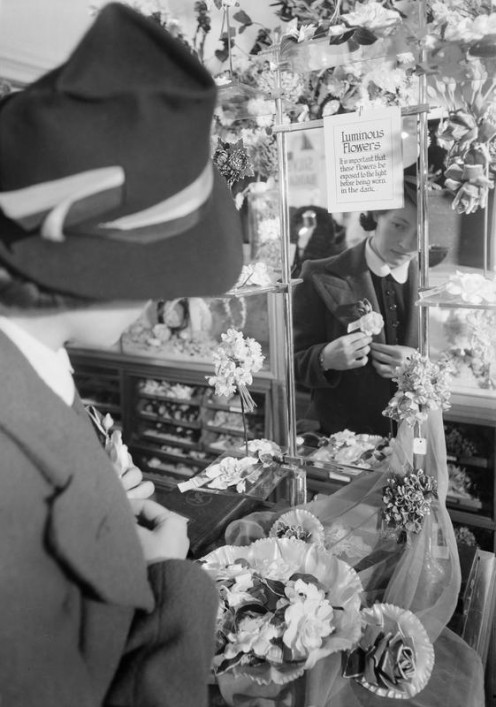 A woman pins a luminous flower to her jacket lapel in Selfridge's department store, London. These flowers were one of numerous blackout accessories available in 1940 to make pedestrians more visible on the dark streets of the capital. http://media.iw