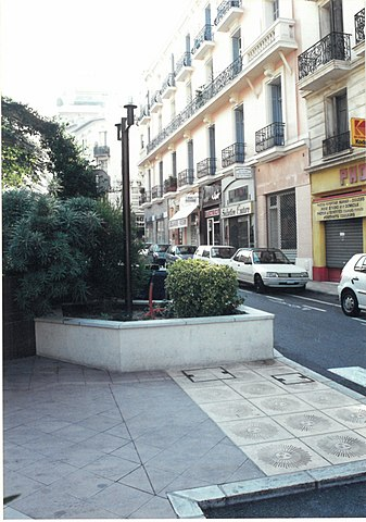 Sidewalk pavement indicating border between France (right, with yellow pavement ties) and Monaco (left grey tiles) on the east side of Boulevard de France (Monaco) or Boulevard du General Leclerc (France), taken in 2000. The buildings in the picture