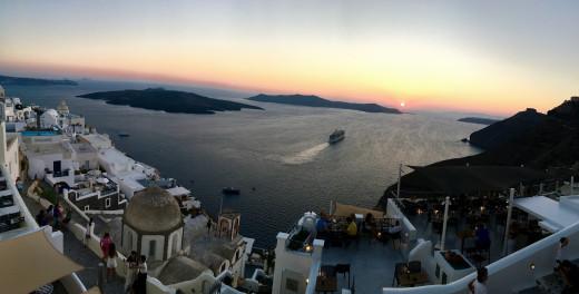 A ship sailing into the sunset at Santorini