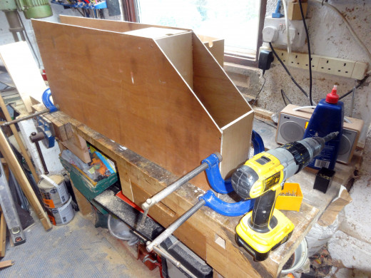 Starting from the top and working down, gluing and screwing the top and drawer supports in place, one at a time, and holding square with clamps until the glue dries.