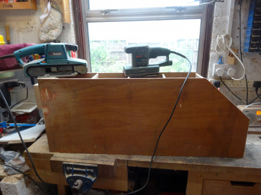 Using a belt and orbital sander to smooth the surfaces and edges, and round off the corners.