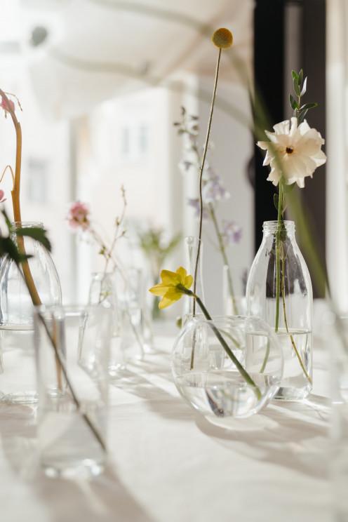Flowers in clear glass bottles.