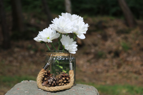 Daisies in jam jar with brown manila rope and twine.