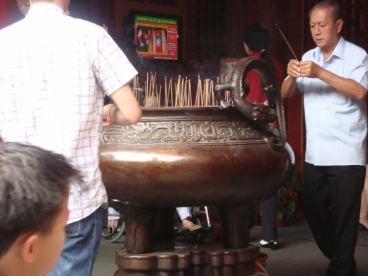 the vat at the entrance with lit joss sticks