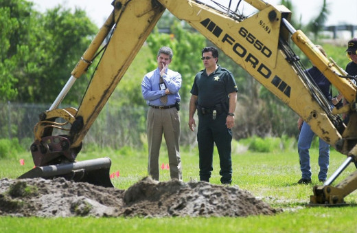Detectives from Orange County Sheriff's Office search a field for the body of Deborah Poe. Photo courtesy of the Orlando Sentinel.