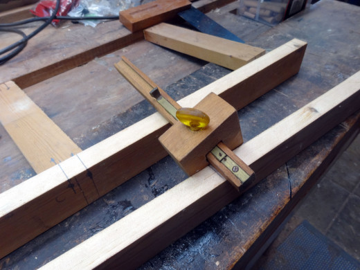 Using a marking gauge to mark where to drill the holes for fitting the dowels.