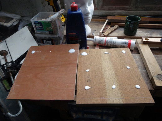 Gluing the white faced hardboard to the shelves.